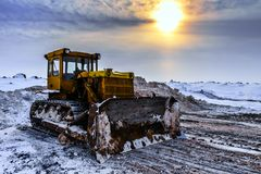 Oude industriële vuile gele tractor onder de avondzon in de bewolkte de winterhemel Stock Foto