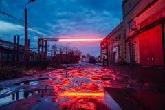 Oude industriezone in avond Vuile pools op gebarsten asfalt van beschadigde weg royalty-vrije stock afbeeldingen