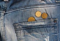 Oude jeans met muntstukken in zak Stock Foto
