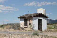 Oude keet op kant van de weg met watertoren Stock Afbeelding