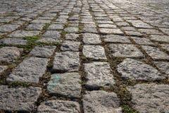Oude keibestrating De straat met graniet cobblestoned bestrating royalty-vrije stock afbeelding