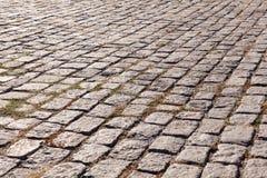 Oude keibestrating De straat met graniet cobblestoned bestrating stock afbeeldingen