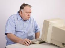 Oude kerel bij computer en knorrig Stock Afbeeldingen