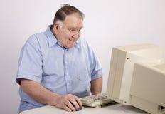 Oude kerel bij computer het grijnzen royalty-vrije stock foto