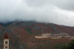 Oude kerk over bergen met rode installaties en wolken in nevelige regenachtige dag Stock Foto