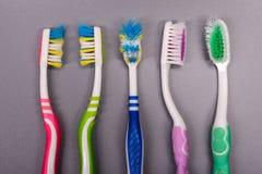 Oude kleurrijke tandenborstels op grijze achtergrond Royalty-vrije Stock Foto's