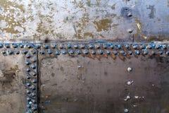 Oude klinknagels op een staalschil Stock Afbeelding