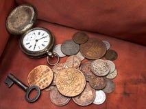 Oude klok, sleutel en muntstukken royalty-vrije stock foto's