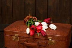 Oude koffer met bloemen, symbool van overwinning in Wereldoorlog II met St George ` s lint, een donkere houten achtergrond, retro Stock Foto