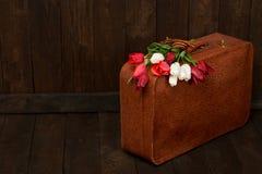 Oude koffer met bloemen, symbool van overwinning in Wereldoorlog II met St George ` s lint, een donkere houten achtergrond, retro Stock Fotografie