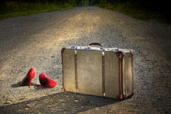 Oude koffer met rode schoenen verlaten op weg Stock Fotografie