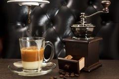 Oude koffiemolen en koffiekop op houten lijst Stock Foto