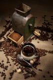 Oude koffiemolen en kop van koffie Royalty-vrije Stock Foto