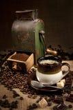 Oude koffiemolen en kop van koffie Royalty-vrije Stock Foto's