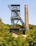 Oude kolenmijntoren en industriële schoorsteen in groen milieu royalty-vrije stock fotografie