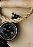 Oude kompas en kabel op grungeachtergrond Stock Foto's