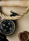 Oude kompas en kabel op grungeachtergrond Stock Fotografie
