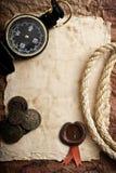 Oude kompas, kabel en muntstukken op grungeachtergrond Stock Foto's