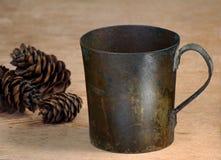 Oude kop van een koper en spar-kegels op een lijst stock foto's
