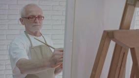 Oude kunstenaar die een beeld in atelier trekken stock videobeelden