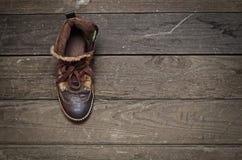 Oude laarzen op de oude raad Stock Afbeeldingen