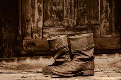 Oude laarzen op een portiek Royalty-vrije Stock Foto's