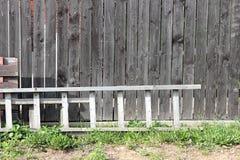 Oude ladder dichtbij een omheining stock fotografie