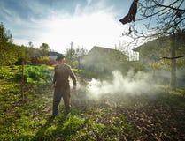 Oude landbouwer die dode bladeren branden Stock Foto
