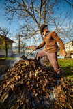 Oude landbouwer die dode bladeren branden Stock Foto's
