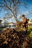 Oude landbouwer die dode bladeren branden Royalty-vrije Stock Foto