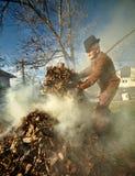Oude landbouwer die dode bladeren branden Royalty-vrije Stock Afbeeldingen