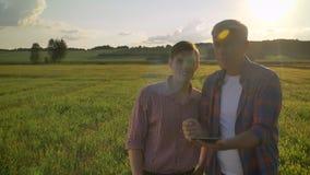 Oude landbouwer die nieuw project met zijn opvolger en tablet houden bespreken, die op tarwegebied zich tijdens mooie zonsonderga stock footage