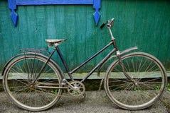 Oude, landelijke fiets dichtbij een houten groene muur royalty-vrije stock afbeelding