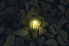 Oude lantaarn in de schuur met brandhout stock foto's