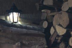 Oude lantaarn in de schuur met brandhout royalty-vrije stock foto's