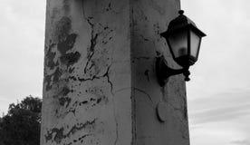 Oude lantaarn op de gebarsten kolom met achtergrond op de hemel stock afbeeldingen