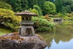 Oude Lantaarn op de vijver in Japanse tuin Stock Foto's