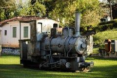 Oude locomotief op het gras met ruïnes op de achtergrond Stock Foto