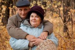 Oude man en oude vrouw met mand in herfstvoorst gedeelte Stock Afbeeldingen