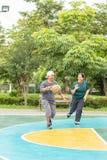 Oude man en vrouw om basketbal in de ochtend zo gelukkig te spelen stock fotografie