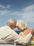 Oude man en vrouw op bank bij het overzees Stock Afbeeldingen