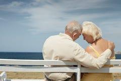 Oude man en vrouw op bank bij het overzees Royalty-vrije Stock Fotografie