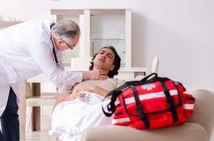 Oude mannelijke arts die jonge mannelijke patiënt bezoeken stock foto