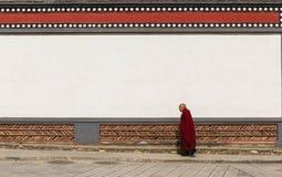 Oude mannelijke lamagang voor traditionele bakstenen muur in anc stock foto