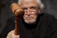 Oude mannelijke rechter in een rechtszaal die de hamer slaan stock afbeelding