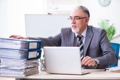 Oude mannelijke werknemer ongelukkig met het bovenmatige werk stock afbeeldingen