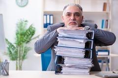 Oude mannelijke werknemer ongelukkig met het bovenmatige werk stock foto
