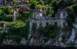 Oude manorruïnes door het van nature overvallen water, bomen royalty-vrije stock foto
