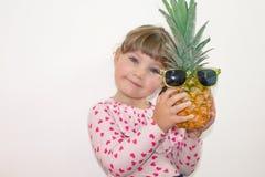 Oude meisje 3 het jaar, houdend een ananas in van hem dient glazen in stock afbeelding