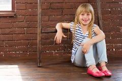 Oude meisje 6 het jaar zit op de vloer naast een bakstenen muur en gevuld met gelach royalty-vrije stock afbeelding